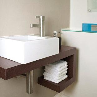 Ejemplo de cuarto de baño principal, minimalista, de tamaño medio, con armarios con paneles lisos, puertas de armario de madera en tonos medios, baldosas y/o azulejos grises, paredes blancas y lavabo bajoencimera