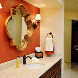 Ispirazione per una grande stanza da bagno padronale tradizionale con lavabo sottopiano, ante con bugna sagomata, ante in legno bruno, top in marmo, vasca sottopiano, doccia doppia, bidè, piastrelle beige, piastrelle in pietra, pareti arancioni e pavimento in gres porcellanato