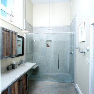 Ejemplo de cuarto de baño principal, industrial, grande, con puertas de armario de madera oscura, ducha doble, sanitario de una pieza, baldosas y/o azulejos grises, baldosas y/o azulejos de cemento, paredes grises, suelo de cemento, lavabo integrado y encimera de vidrio reciclado