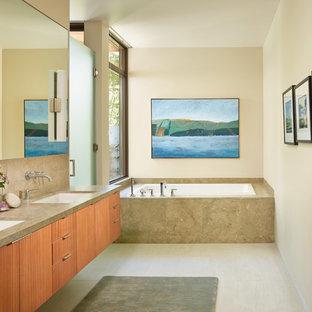 Свежая идея для дизайна: ванная комната в современном стиле с плоскими фасадами, фасадами цвета дерева среднего тона, накладной ванной, бежевой плиткой, бежевыми стенами, врезной раковиной и плиткой из известняка - отличное фото интерьера