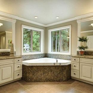 Immagine di una stanza da bagno padronale classica con ante con bugna sagomata, ante bianche, vasca idromassaggio, pareti beige, pavimento in gres porcellanato, lavabo sottopiano e top in granito