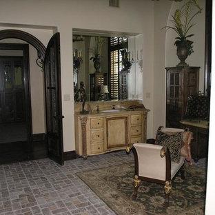 Foto di una grande stanza da bagno mediterranea con lavabo da incasso, ante in legno chiaro, pareti bianche, pavimento in mattoni e pavimento marrone