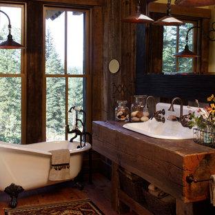 Imagen de cuarto de baño con ducha, rústico, pequeño, con armarios abiertos, puertas de armario de madera oscura, bañera con patas, paredes marrones, suelo de madera en tonos medios, lavabo de seno grande, encimera de madera, suelo marrón y encimeras marrones