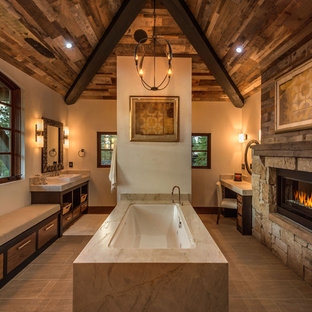Foto på ett mellanstort rustikt beige en-suite badrum, med ett fristående handfat, släta luckor, skåp i mellenmörkt trä, ett undermonterat badkar, beige väggar, brun kakel, porslinskakel, klinkergolv i porslin, bänkskiva i kvarts och beiget golv