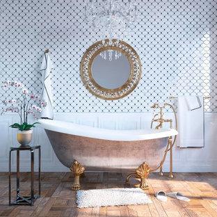 Foto di una grande stanza da bagno padronale boho chic con vasca con piedi a zampa di leone, WC a due pezzi, piastrelle bianche, piastrelle a mosaico, pareti bianche, pavimento in legno massello medio e pavimento marrone