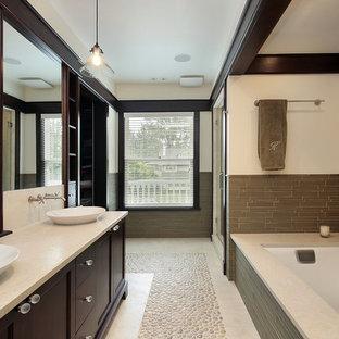 ミネアポリスの大きいアジアンスタイルのおしゃれなマスターバスルーム (シェーカースタイル扉のキャビネット、茶色いキャビネット、ドロップイン型浴槽、アルコーブ型シャワー、ベージュの壁、玉石タイル、ベッセル式洗面器、ライムストーンの洗面台、ベージュの床、開き戸のシャワー) の写真