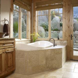 Elegant travertine tile drop-in bathtub photo in Denver with a vessel sink