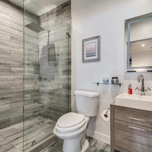 Immagine di una piccola stanza da bagno con doccia minimal con WC a due pezzi, pavimento con piastrelle in ceramica, pavimento grigio, doccia aperta, ante lisce, ante grigie, doccia alcova, piastrelle grigie e lavabo a bacinella
