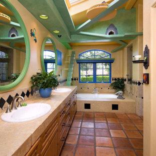 Diseño de cuarto de baño bohemio con lavabo encastrado, armarios estilo shaker, puertas de armario de madera oscura, ducha esquinera, baldosas y/o azulejos beige, baldosas y/o azulejos de piedra, paredes beige, suelo de baldosas de terracota y bañera encastrada sin remate