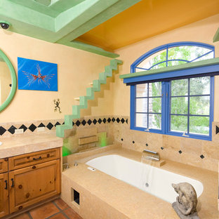 Example of an eclectic beige tile and stone tile terra-cotta floor bathroom design in Santa Barbara with shaker cabinets, medium tone wood cabinets, a hot tub and beige walls