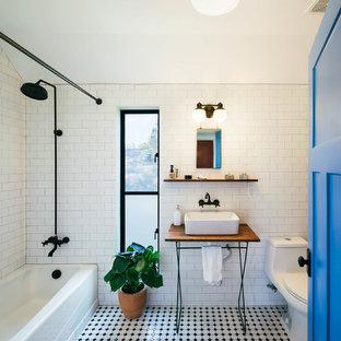 Ispirazione per una stanza da bagno industriale con lavabo a bacinella, top in legno, vasca ad alcova, vasca/doccia, WC monopezzo, piastrelle bianche, piastrelle diamantate, pavimento multicolore e top marrone