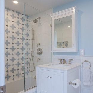 Idéer för att renovera ett litet funkis vit vitt badrum för barn, med skåp i shakerstil, vita skåp, ett undermonterat badkar, en dusch/badkar-kombination, en vägghängd toalettstol, vit kakel, marmorkakel, blå väggar, mosaikgolv, ett undermonterad handfat, marmorbänkskiva, vitt golv och med dusch som är öppen