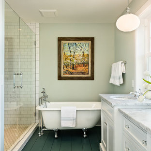Idée de décoration pour une douche en alcôve principale tradition de taille moyenne avec un placard avec porte à panneau encastré, des portes de placard blanches, une baignoire sur pieds, un carrelage blanc, un carrelage métro, un lavabo encastré, un sol vert, une cabine de douche à porte battante, un mur vert, un sol en bois peint, un plan de toilette en marbre et un plan de toilette blanc.