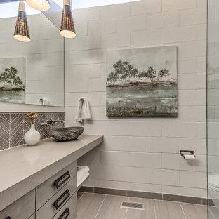 Idee per una stanza da bagno con doccia design di medie dimensioni con ante lisce, ante grigie, doccia ad angolo, WC monopezzo, piastrelle grigie, piastrelle di vetro, pareti bianche, pavimento in gres porcellanato, lavabo a bacinella, top in quarzite e top grigio