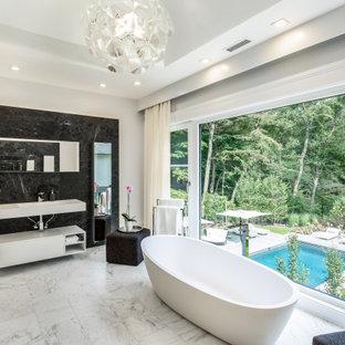 Идея дизайна: ванная комната в современном стиле с плоскими фасадами, белыми фасадами, отдельно стоящей ванной, черной плиткой, белыми стенами, монолитной раковиной, разноцветным полом, белой столешницей, тумбой под одну раковину, подвесной тумбой и многоуровневым потолком