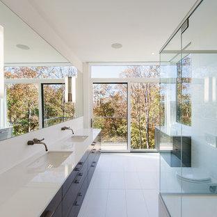 Foto de cuarto de baño minimalista, grande, con armarios con paneles lisos, puertas de armario de madera en tonos medios, ducha esquinera, sanitario de pared, baldosas y/o azulejos blancos, paredes blancas, lavabo bajoencimera y suelo de baldosas de cerámica