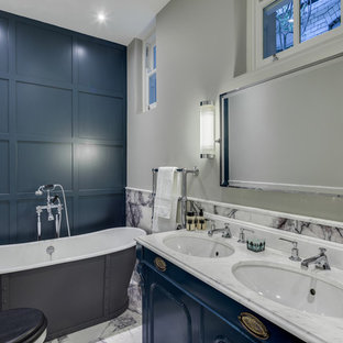Medium sized traditional ensuite bathroom in London with a submerged sink, blue cabinets, marble worktops, a freestanding bath, a two-piece toilet, white tiles, stone tiles, grey walls, marble flooring and freestanding cabinets.