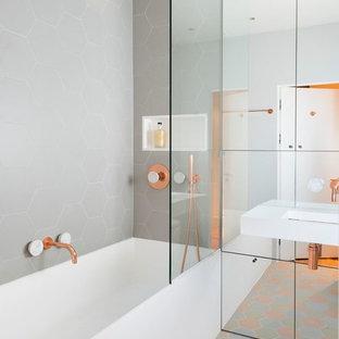 Kleines Modernes Badezimmer mit grauen Fliesen, Wandwaschbecken, Badewanne in Nische, buntem Boden und offener Dusche in London
