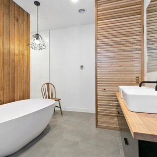 Design ideas for a mid-sized contemporary master bathroom in Geelong with flat-panel cabinets, black cabinets, a freestanding tub, an open shower, white tile, ceramic tile, white walls, cement tiles, a vessel sink, wood benchtops, grey floor, an open shower, beige benchtops, a niche, a double vanity, a floating vanity and wood walls.