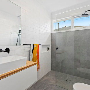 Inspiration for a mid-sized contemporary bathroom in Geelong with white walls, wood benchtops, flat-panel cabinets, white cabinets, a curbless shower, gray tile, a vessel sink, grey floor and brown benchtops.