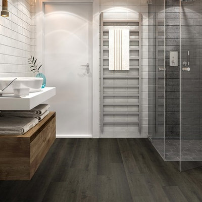 Example of a mid-sized trendy 3/4 gray tile dark wood floor and black floor corner shower design in Orange County with white walls, a vessel sink, solid surface countertops, a hinged shower door and white countertops