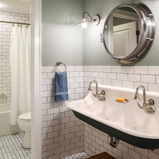 Inspiration for a medium sized rural family bathroom in Milwaukee with a trough sink, an alcove bath, a shower/bath combination, white tiles, ceramic tiles, green walls and mosaic tile flooring.