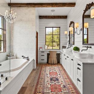 На фото: ванная комната в стиле кантри с фасадами с выступающей филенкой, белыми фасадами, накладной ванной, серой плиткой, мраморной плиткой, белыми стенами, паркетным полом среднего тона, настольной раковиной, мраморной столешницей, бежевым полом, душем с распашными дверями, серой столешницей, тумбой под две раковины, встроенной тумбой, балками на потолке и стенами из вагонки с