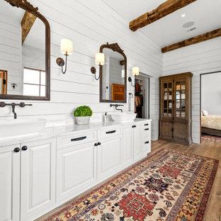 Идея дизайна: ванная комната в стиле кантри с фасадами с выступающей филенкой, белыми фасадами, накладной ванной, серой плиткой, мраморной плиткой, белыми стенами, паркетным полом среднего тона, настольной раковиной, мраморной столешницей, бежевым полом, душем с распашными дверями, серой столешницей, тумбой под две раковины, балками на потолке и стенами из вагонки