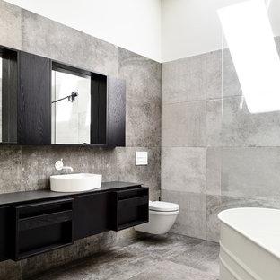 Inspiration för mellanstora moderna svart badrum med dusch, med ett fristående badkar, en vägghängd toalettstol, grå kakel, keramikplattor, klinkergolv i keramik, grått golv, kaklad bänkskiva, släta luckor, svarta skåp, vita väggar och ett fristående handfat