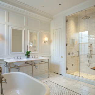 Design ideas for a traditional ensuite bathroom in DC Metro with a freestanding bath, white tiles, ceramic tiles, white walls, marble flooring, marble worktops and a console sink.