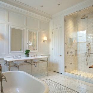 ワシントンD.C.のトラディショナルスタイルのおしゃれなマスターバスルーム (置き型浴槽、白いタイル、セラミックタイル、白い壁、大理石の床、大理石の洗面台、コンソール型シンク) の写真