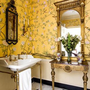 Ispirazione per una stanza da bagno chic di medie dimensioni con pavimento in marmo, lavabo a consolle, pavimento bianco e pareti gialle