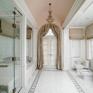 Пример оригинального дизайна: большая главная ванная комната в классическом стиле с белыми фасадами, полновстраиваемой ванной, душем в нише, белой плиткой, каменной плиткой, розовыми стенами, полом из керамической плитки, мраморной столешницей, фасадами с утопленной филенкой, биде, душем с распашными дверями, врезной раковиной, белым полом и белой столешницей