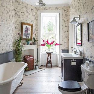Imagen de cuarto de baño infantil, clásico, grande, con bañera con patas, suelo de madera oscura, lavabo tipo consola, suelo marrón, armarios con rebordes decorativos, puertas de armario grises, sanitario de una pieza, encimera de laminado y encimeras blancas