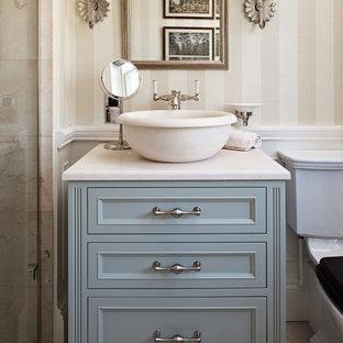他の地域のトラディショナルスタイルのおしゃれな浴室 (家具調キャビネット、青いキャビネット、ベージュの壁、ベッセル式洗面器、ベージュの床、ベージュのカウンター) の写真