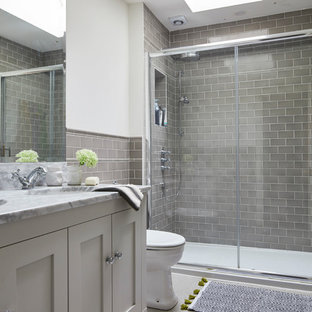 Inspiration for a large transitional 3/4 wet room bathroom in Dublin with recessed-panel cabinets, grey cabinets, gray tile, grey walls, marble benchtops and a sliding shower screen.