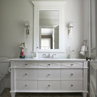 Example of a mid-sized classic 3/4 porcelain tile and beige floor bathroom design in New York with furniture-like cabinets, white cabinets, a two-piece toilet, white walls, an undermount sink and marble countertops
