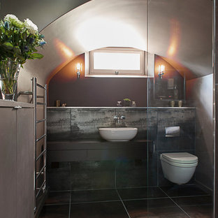 This is an example of a contemporary shower room in Kent with flat-panel cabinets, brown cabinets, a built-in shower, a wall mounted toilet, brown tiles, brown walls, a vessel sink and an open shower.