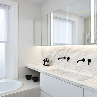 Photo of a large modern ensuite bathroom in London with flat-panel cabinets, white cabinets, a built-in bath, white walls, porcelain flooring, marble worktops, grey floors, multi-coloured worktops, multi-coloured tiles, stone slabs and a trough sink.