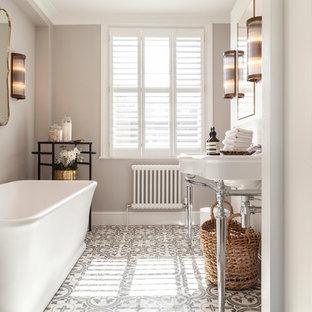 Medium sized classic bathroom in London with a freestanding bath, a shower/bath combination, grey walls, a console sink and grey floors.