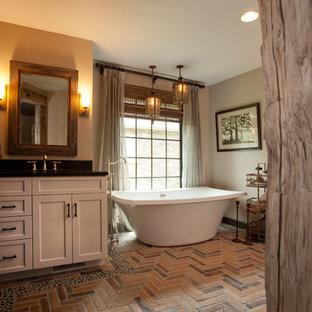 Ejemplo de cuarto de baño principal, rural, de tamaño medio, con armarios estilo shaker, puertas de armario blancas, bañera exenta, paredes beige, suelo de ladrillo y lavabo bajoencimera