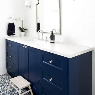 Transitional bathroom in Brisbane with recessed-panel cabinets, blue cabinets, white tile, white walls, an undermount sink, multi-coloured floor and white benchtops.