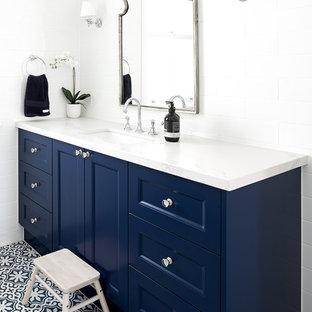 Modelo de cuarto de baño tradicional renovado con armarios con paneles empotrados, puertas de armario azules, baldosas y/o azulejos blancos, paredes blancas, lavabo bajoencimera, suelo multicolor y encimeras blancas