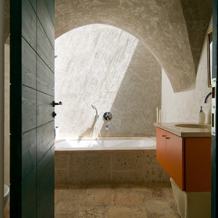 Design ideas for a mediterranean ensuite bathroom in Other with an integrated sink, flat-panel cabinets, orange cabinets, a submerged bath, an alcove shower, beige tiles, beige walls and slate flooring.