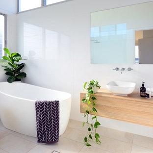 Стильный дизайн: ванная комната среднего размера в стиле модернизм с фасадами с утопленной филенкой, светлыми деревянными фасадами, отдельно стоящей ванной, белой плиткой и столешницей из дерева - последний тренд
