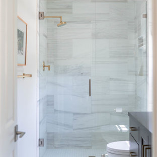 Small trendy 3/4 beige tile and porcelain tile marble floor and white floor alcove shower photo in San Diego with shaker cabinets, gray cabinets, a one-piece toilet, white walls, solid surface countertops, a hinged shower door and gray countertops