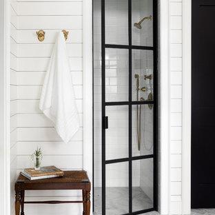 Ejemplo de cuarto de baño campestre con ducha empotrada, baldosas y/o azulejos blancos, baldosas y/o azulejos de cemento, paredes blancas, suelo gris y ducha con puerta con bisagras