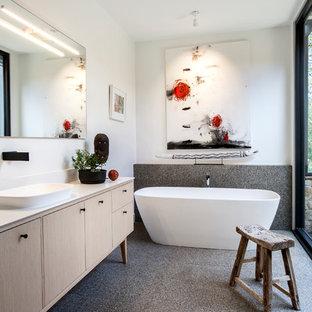 Esempio di una grande stanza da bagno padronale minimal con vasca freestanding, doccia ad angolo, WC sospeso, pareti bianche, pavimento alla veneziana, lavabo integrato, top in superficie solida e doccia aperta