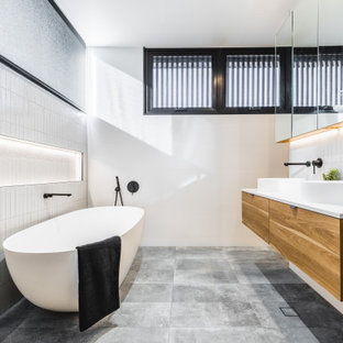 Photo of a contemporary bathroom in Other with flat-panel cabinets, medium wood cabinets, a freestanding tub, white tile, white walls, a vessel sink, grey floor, white benchtops, a double vanity, a floating vanity and a niche.