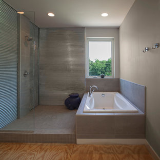 This is an example of a modern master bathroom in Other with a drop-in tub, an open shower, gray tile, ceramic tile, grey walls, plywood floors and tile benchtops.